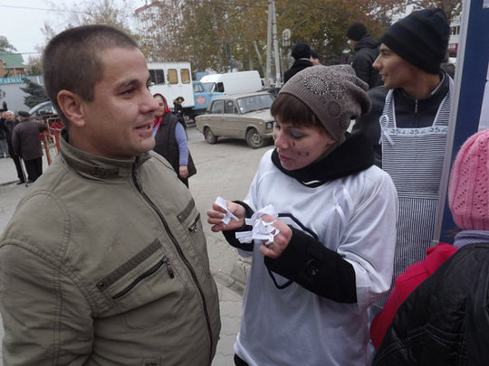 A volunteer offers white ribbons to passersby