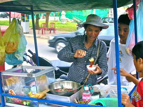 Cambodian woman serving food in a street market