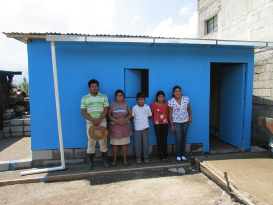 Some of Jose's family in front of their new home