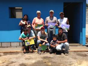 The family & volunteers in front of the new home