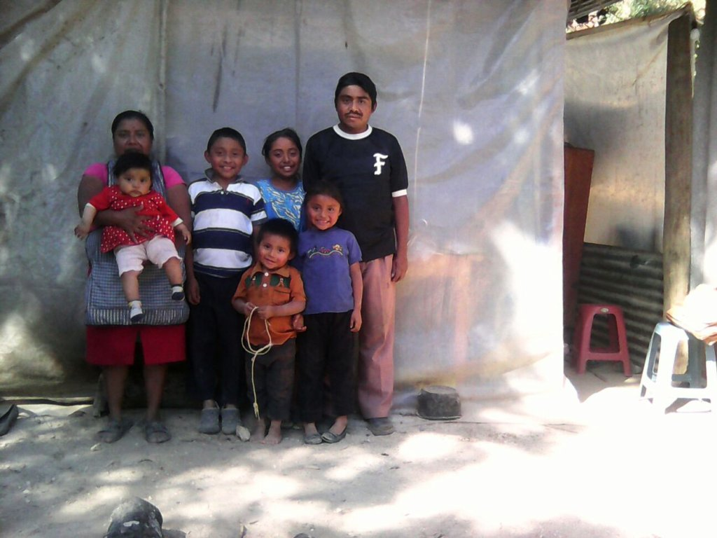 Cristobal and his family next to their old home.
