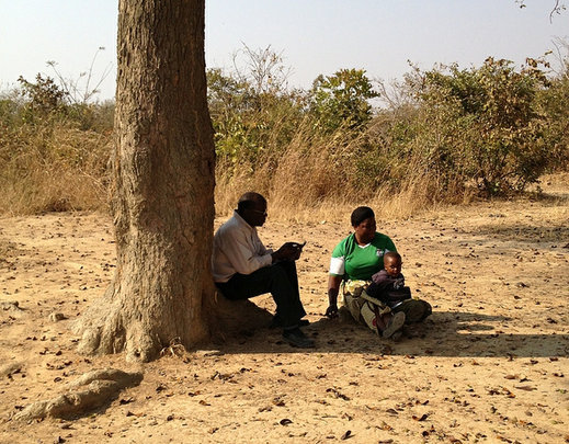 Mr Banda interviews a mother, shaded by a tree.