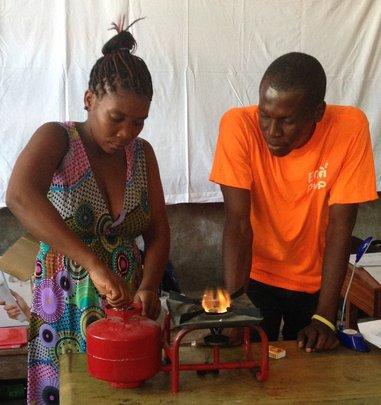 Magalie practices using an improved kerosene stove