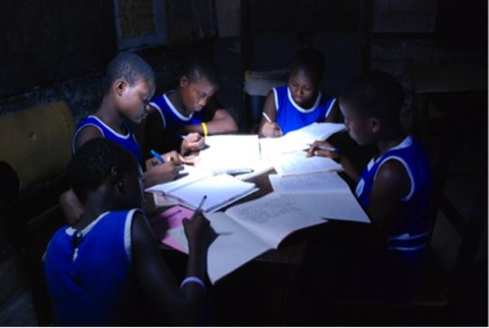 School children studying at night with solar light