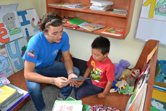 A volunteer helping one of our children read