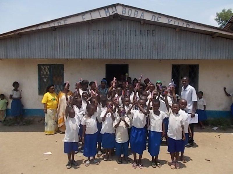 Kids in Kiliba proudly display their writing tools