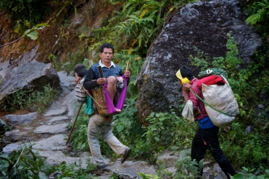 A patient is carried through the Himalayan trails