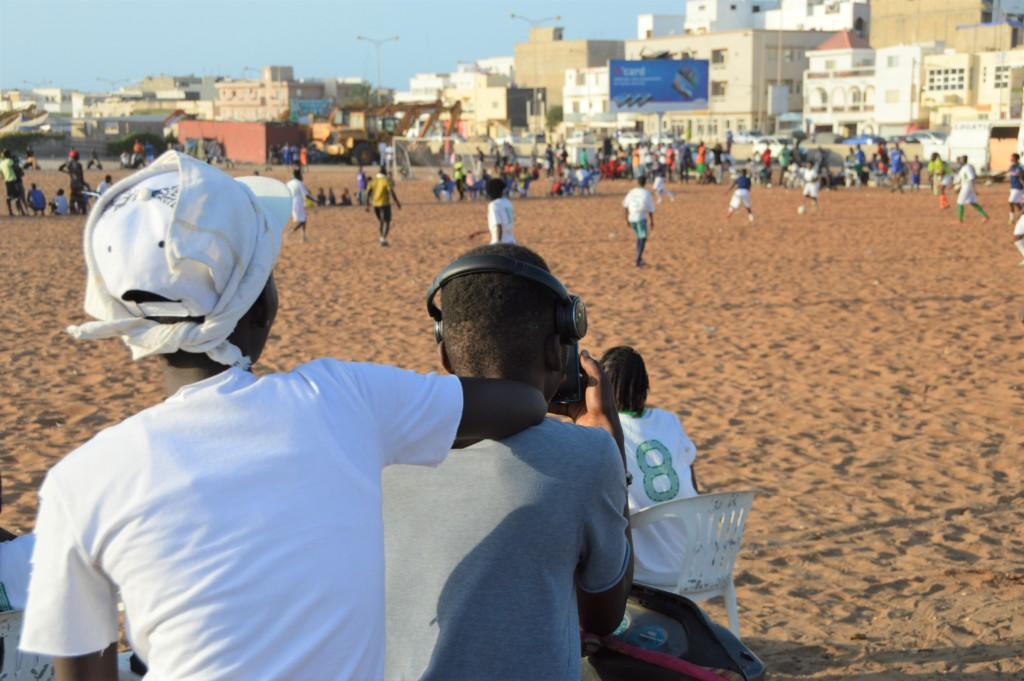 Spectators surround the field to watch.