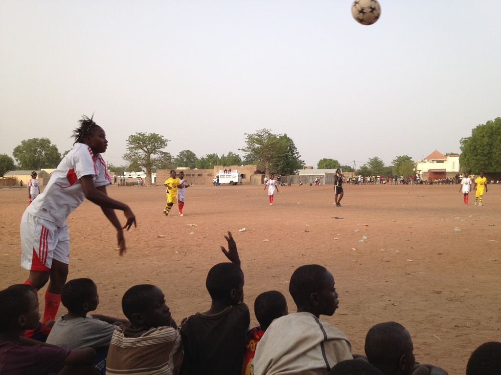 Amazone player throws in the ball before some fans