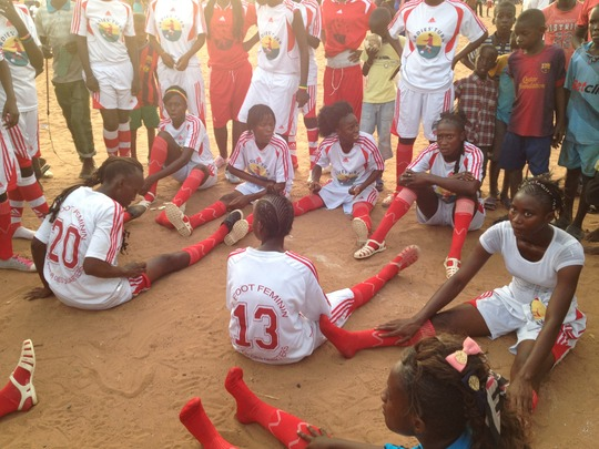 Girls stretch and discuss strategy for the game.