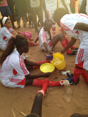 Kaffrine players share water during a hot game.
