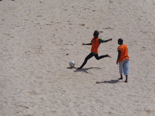 Soccer in Senegal is a sandy sport. Power kick!
