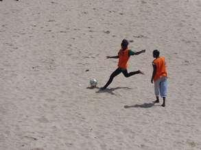 Soccer in Senegal is a sandy sport. Power kick!