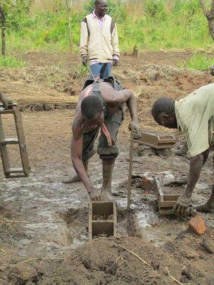 Men putting mud into brick molds
