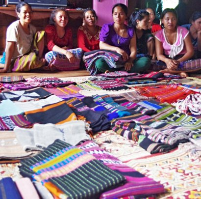 Artisans show handwoven fabrics they made to sell.
