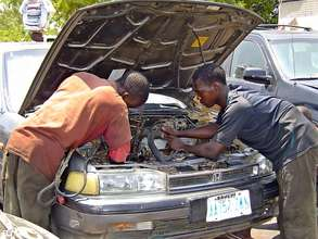 Beneficiaries learning how to repair a car