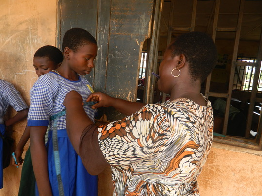 Tailor taking measurents for uniform