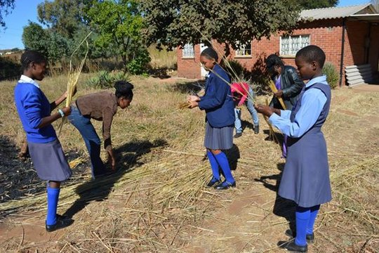 Nkulumane students cutting straw for their bags