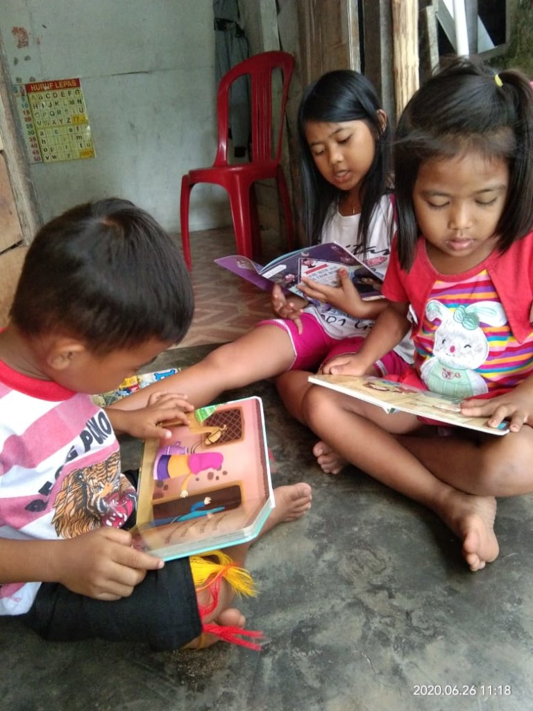 Reading together at home with their siblings