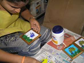 A beneficiary making a mosaic coaster