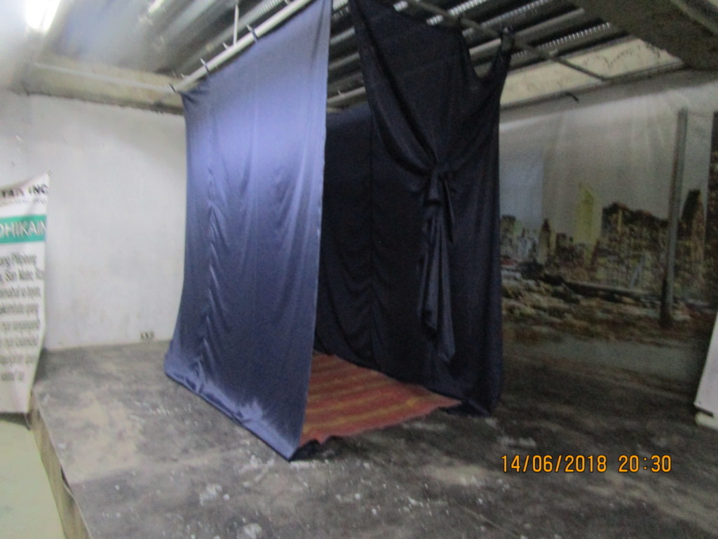 A cubicle completed with curtains and bedding