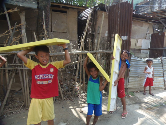 Kids lend a hand by carrying the boat seats