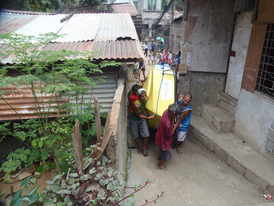 Residents carry the boat through narrow alleyways