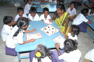 Para teacher helping children to read