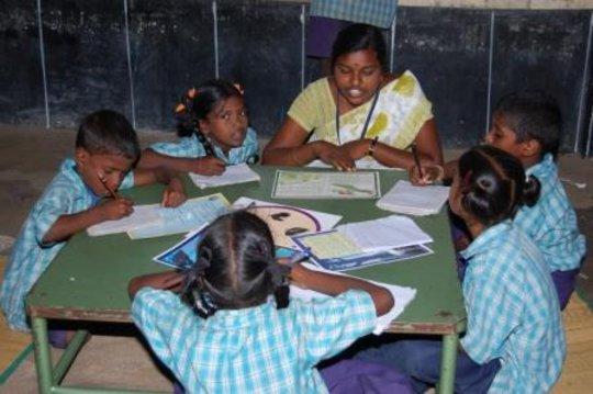 Para teacher helping children to read