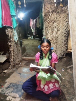 Piya studying in front of her home
