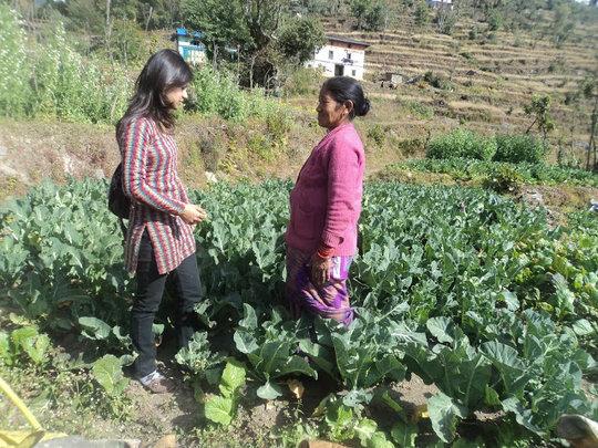 ETC staff member visiting a farmer in her garden