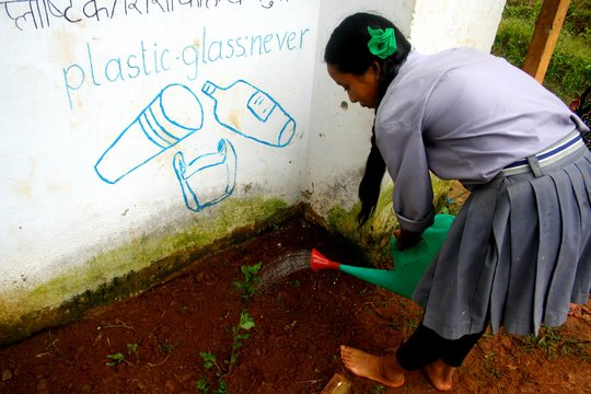 Sushila watering the plants.
