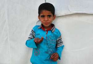 Syrian refugee child outside his family tent