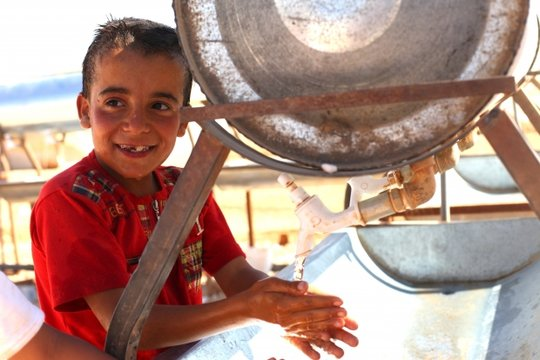 A refugee boy using Mercy Corps provided water