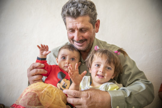 Ahmad, 51, holding his granddaughters