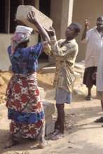 A woman being helped to carry a cement block to li