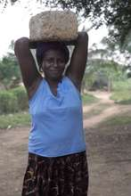 A woman carrying a cement block to library site