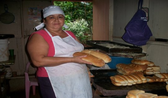 Heliodora Cardoza, a beneficiary, baking bread