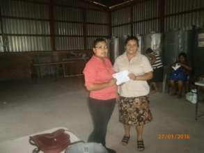 Yolanda (L) issues a micro-loan to Migdalia (R)