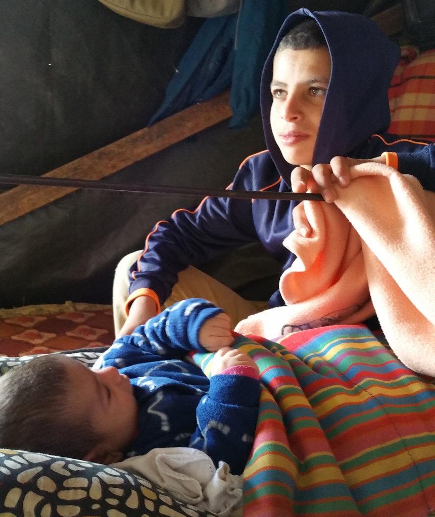 Aysar, at home with his new sister, in Susiya