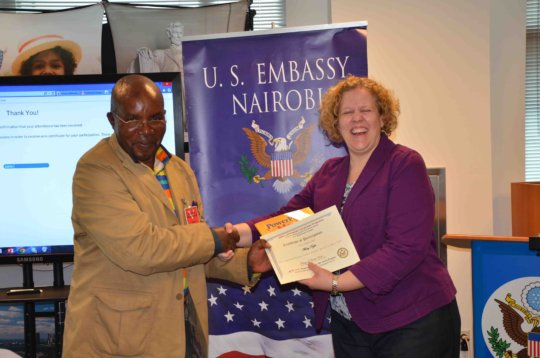 A teacher recieves a cerficate at the US embassy