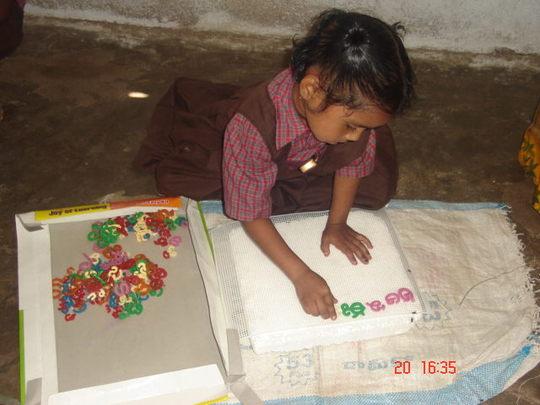 Girl child is practicing Telugu Alphabets