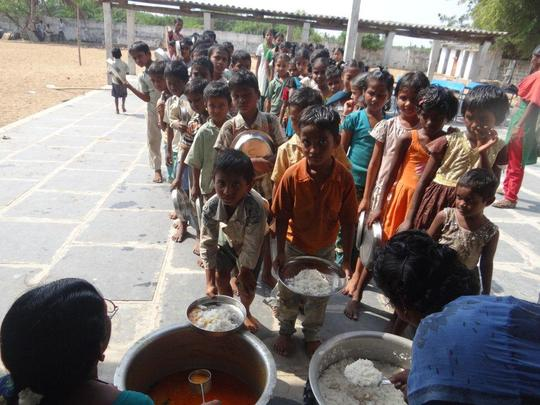 Children stand in line to receive their meal