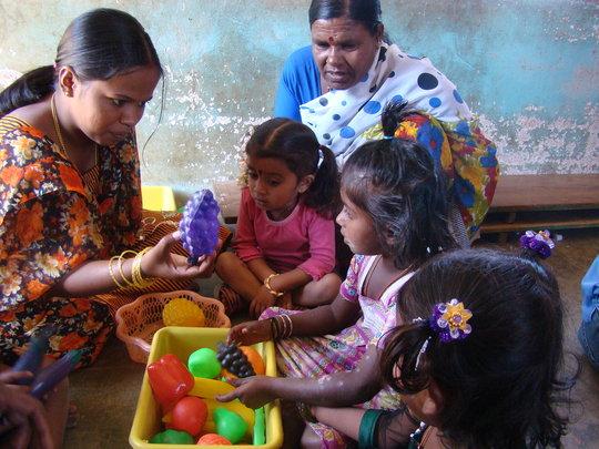 Teacher teaching about fruits to children