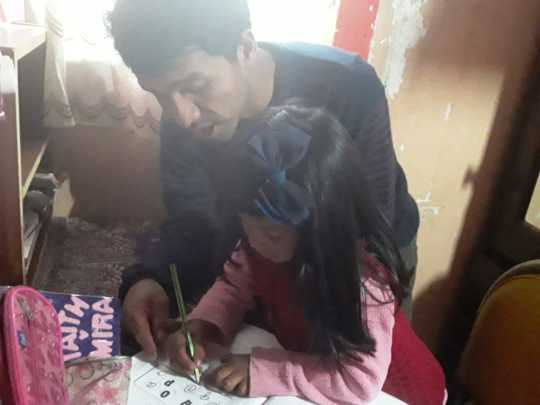Father helps his young daughter