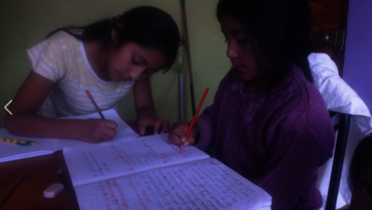 Girls study with siblings during home school