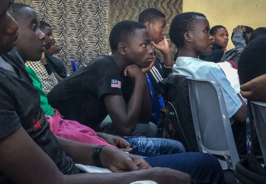 Students watch Isano Isangiwe's performance.