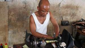 A man receiving tailoring skills training