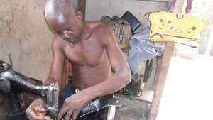 A man receiving training on how to sew bags