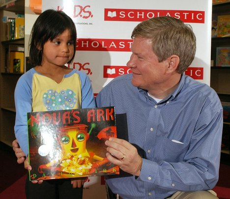 A young girl receiving a book from Scholastic